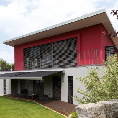 Außenjalousien an einem roten Haus